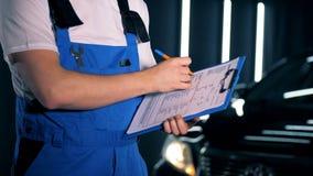 Ein Mechanikerschreiben während einer Inspektion Eine Service-Arbeitskraft hält ein Klemmbrett und schreibt auf es stock video footage