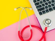 Ein medizinisches Stethoskop und ein Laptop auf einem rosa und gelben Tabellenhintergrund Lizenzfreie Stockfotografie