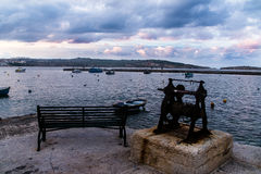 Ein Meerblick mit einem bewölkten Himmel und eine Bank und eine alte Bootswinde im Vordergrund Stockbilder