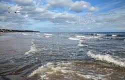 Ein Meerblick mit einem sandigen Strand und mildern Wellen Lizenzfreie Stockfotos
