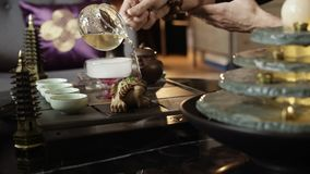 Ein Meister von Teezeremonien verschüttet Tee und die Bewässerung eines Frosches stock video