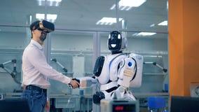 Ein Mensch und ein menschlich ähnlicher Android rütteln Hände und aufpassende virtuelle Realität stock video footage