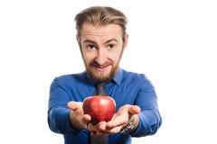 Ein merkwürdiger Büromann mit einem Großkopf bietet einen Apfel an umgewandeltes Bild Stockfotografie