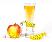 Ein messendes Band des Gelbs, das roten Apfel und Saft einwickelt Stockbild
