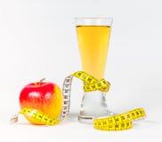Ein messendes Band des Gelbs, das roten Apfel und Saft einwickelt Stockfoto