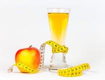 Ein messendes Band des Gelbs, das roten Apfel und Saft einwickelt Stockbilder