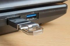 Ein Metallblitz-Antrieb im usb-Schlitz einer Laptopnahaufnahme Stockfotos