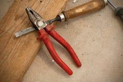 Ein metallischer Meißel und Zangen mit rotem Griff auf dem hölzernen Brett stockfotos