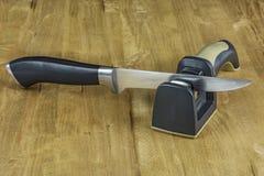 Ein Metallmesser und ein Bleistiftspitzer auf einer Holzoberfläche Lizenzfreie Stockbilder