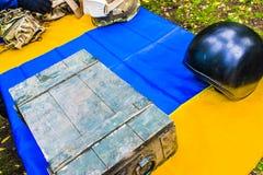 Ein Metallsturzhelm und eine kugelsichere Weste legen auf eine blaue gelbe Flagge stockfotografie