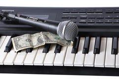 Ein Mikrofon und ein Dollar, die auf den Tasten liegen Stockbild