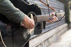 Ein Mischrassemann, der Gitarre in der Straße spielt lizenzfreie stockfotografie