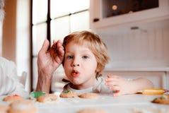Ein Mittelteil der älteren Großmutter mit dem kleinen Kleinkindjungen, der zu Hause Kuchen macht lizenzfreies stockbild