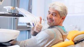 Ein mittlerer gealterter junger gutaussehender Mann, der in einem Zahnarztstuhl sitzt, macht er Lächeln zu Kamera und zeigt sich  stock video footage