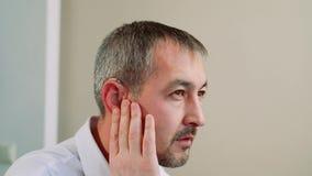 Ein mittlerer gealterter Mann versucht auf einem Hörgerät stock video