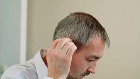 Ein mittlerer gealterter Mann versucht auf einem Hörgerät stock footage