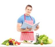 Ein männlicher Chef, der ein Kochbuch bei der Zubereitung eines Salats liest Lizenzfreie Stockfotografie