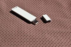 Ein moderner tragbarer Adapter USBs Wi-Fi wird auf die braune Sportkleidung gesetzt, die von Polyester-Nylon fibe hergestellt wir Lizenzfreie Stockfotografie