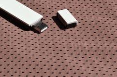 Ein moderner tragbarer Adapter USBs Wi-Fi wird auf die braune Sportkleidung gesetzt, die von Polyester-Nylon fibe hergestellt wir Stockbild