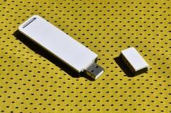 Ein moderner tragbarer Adapter USBs Wi-Fi wird auf die gelbe Sportkleidung gesetzt, die von Polyester-Nylon fibe hergestellt wird Lizenzfreie Stockbilder