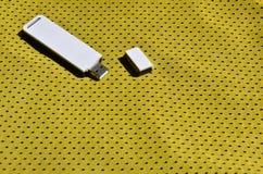 Ein moderner tragbarer Adapter USBs Wi-Fi wird auf die gelbe Sportkleidung gesetzt, die von Polyester-Nylon fibe hergestellt wird Stockbild