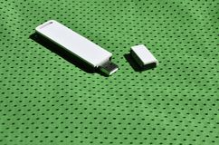 Ein moderner tragbarer Adapter USBs Wi-Fi wird auf die grüne Sportkleidung gesetzt, die von Polyester-Nylon fibe hergestellt wird Stockbilder