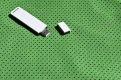 Ein moderner tragbarer Adapter USBs Wi-Fi wird auf die grüne Sportkleidung gesetzt, die von Polyester-Nylon fibe hergestellt wird Stockbild