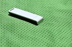 Ein moderner tragbarer Adapter USBs Wi-Fi wird auf die grüne Sportkleidung gesetzt, die von Polyester-Nylon fibe hergestellt wird Lizenzfreies Stockbild