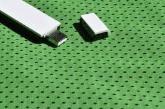Ein moderner tragbarer Adapter USBs Wi-Fi wird auf die grüne Sportkleidung gesetzt, die von Polyester-Nylon fibe hergestellt wird Stockfotografie