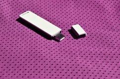 Ein moderner tragbarer Adapter USBs Wi-Fi wird auf die purpurrote Sportkleidung gesetzt, die von Polyester-Nylon fibe hergestellt Stockfoto