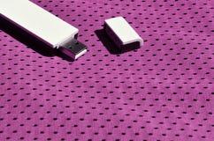 Ein moderner tragbarer Adapter USBs Wi-Fi wird auf die purpurrote Sportkleidung gesetzt, die von Polyester-Nylon fibe hergestellt Stockfotografie