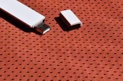 Ein moderner tragbarer Adapter USBs Wi-Fi wird auf die rote Sportkleidung gesetzt, die von Polyester-Nylon fibe hergestellt wird Stockfotos