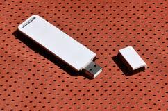 Ein moderner tragbarer Adapter USBs Wi-Fi wird auf die rote Sportkleidung gesetzt, die von Polyester-Nylon fibe hergestellt wird Lizenzfreie Stockfotos