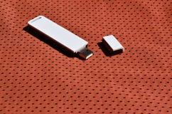 Ein moderner tragbarer Adapter USBs Wi-Fi wird auf die rote Sportkleidung gesetzt, die von Polyester-Nylon fibe hergestellt wird Lizenzfreie Stockfotografie