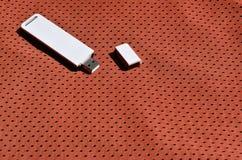 Ein moderner tragbarer Adapter USBs Wi-Fi wird auf die rote Sportkleidung gesetzt, die von Polyester-Nylon fibe hergestellt wird Stockfoto