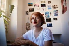 Ein moderner weiblicher Mitarbeiter, der während des Arbeitsprozesses lächelt Junges Hippie-Start-Projekt Kurzes Haar und Weiß de Stockfotografie