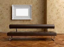 Ein modernes braunes Sofa und ein Anstrich auf der Wand Lizenzfreie Stockfotografie