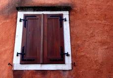 Ein modernes hölzernes dunkelbraunes geschlossenes Fenster mit weißem Rahmen auf einem r Lizenzfreie Stockfotografie