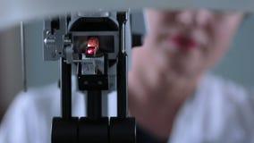 Ein modernes medizinisches Gerät für die Augenprüfung Unerkennbarer Doktor, der mit geduldiger Augenprüfung arbeitet stock video footage