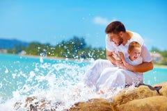 Ein Moment des Wassers spritzend auf glücklichem Vater und Sohn Stockfotografie