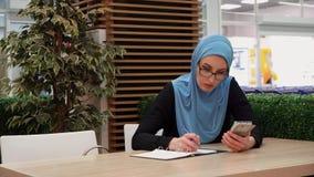 Ein moslemisches Mädchen schreibt in ein Notizbuch, das in einem Café mit einem Telefon sitzt stock video