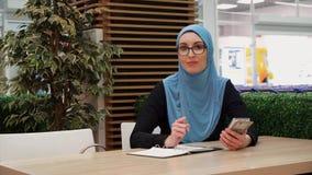 Ein moslemisches Mädchen schreibt in ein Notizbuch, das in einem Café mit einem Telefon sitzt, betrachtet die Kamera stock video