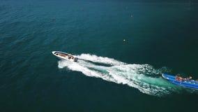 Ein Motorboot, das ein Bananenboot mit Touristen zieht Die Touristenorte in Russland für entspannen sich, Küste Schwarzen Meers v stock footage