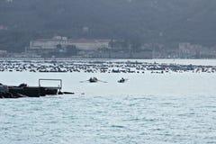 Ein Motorboot und ein Ruderboot kommen den Hafen von La Spezia stockbild