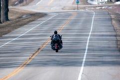 Ein Motorrad auf einer Land-Straße Lizenzfreie Stockfotos