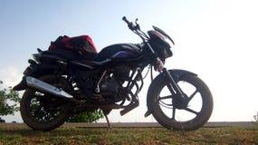Ein Motorrad mit Himmel und Gras und Straße neben ihr Stockfoto