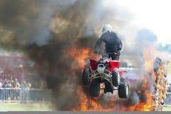 Ein Motorradfahrer auf einem Leitungsfahrrad, das durch Feuer springt Lizenzfreies Stockbild