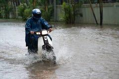 Ein Motorradfahrer reitet entlang eine überschwemmte Straße in Hanoi-Stadt, Vietnam Lizenzfreies Stockbild