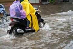 Ein Motorradfahrer reitet entlang eine überschwemmte Straße in Hanoi-Stadt, Vietnam Lizenzfreie Stockfotos