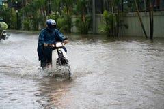 Ein Motorradfahrer reitet entlang eine überschwemmte Straße in Hanoi-Stadt, Vietnam Stockfoto